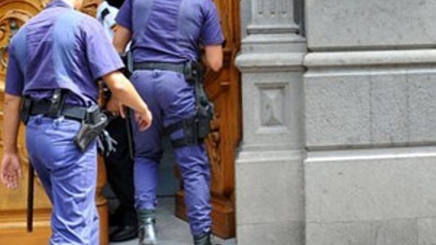 Dos agentes de la Policía Judicial entran en las dependencias de la Mutua de Accidentes de Canarias en la capital tinerfeña. (ACFI PRESS)