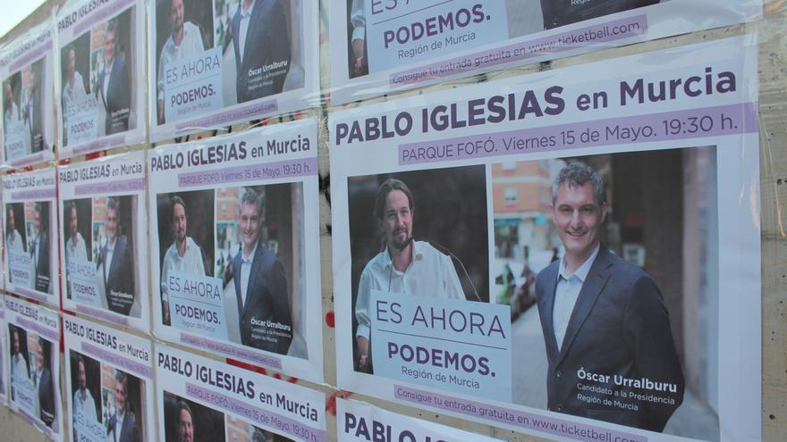 Carteles con Pablo Iglesias y Óscar Urralburu, junto al escenario del acto de Podemos / PSS