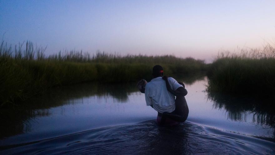 Un miembro de MSF ayuda a un joven y a su familia a cruzar los pantanos en la isla de Kok, en Sudán del Sur, en pleno atardecer. Tras varios meses y por primera vez, acaban de recibir una distribución de alimentos en el problemático estado de Unidad, al norte del país. Una escalada del conflicto en el estado de Unidad obligó a cientos de miles de personas a abandonar sus hogares. Muchos se escondieron en el bosque y en zonas pantanosas. Según los testimonios recogidos por MSF, se produjeron ejecuciones, violaciones en masa y secuestros y pueblos enteros fueron destruidos. © Dominic Nahr