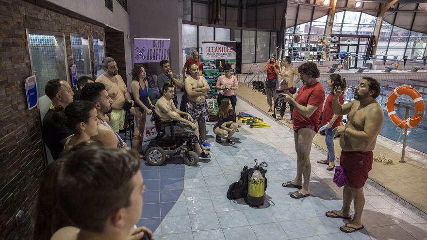 Los participantes escuchan las indicaciones antes se sumergirse en la piscina. / O. M.