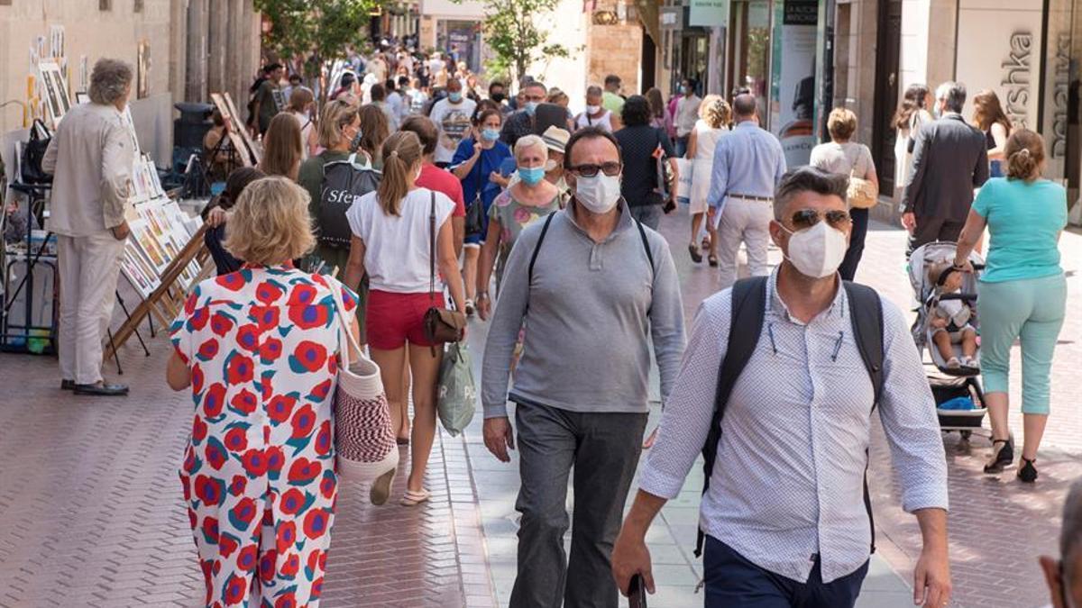 Transeúntes se protegen con mascarillas por las calles de Palma.