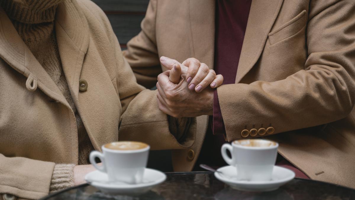 Un hombre le sujeta la mano a su mujer.