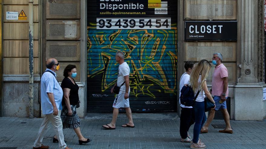Varias personas pasean por una calle en Barcelona.