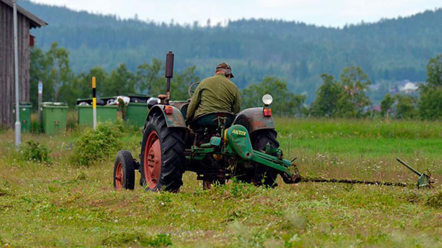 Un trabajador en un tractor con apero   PIXABAY
