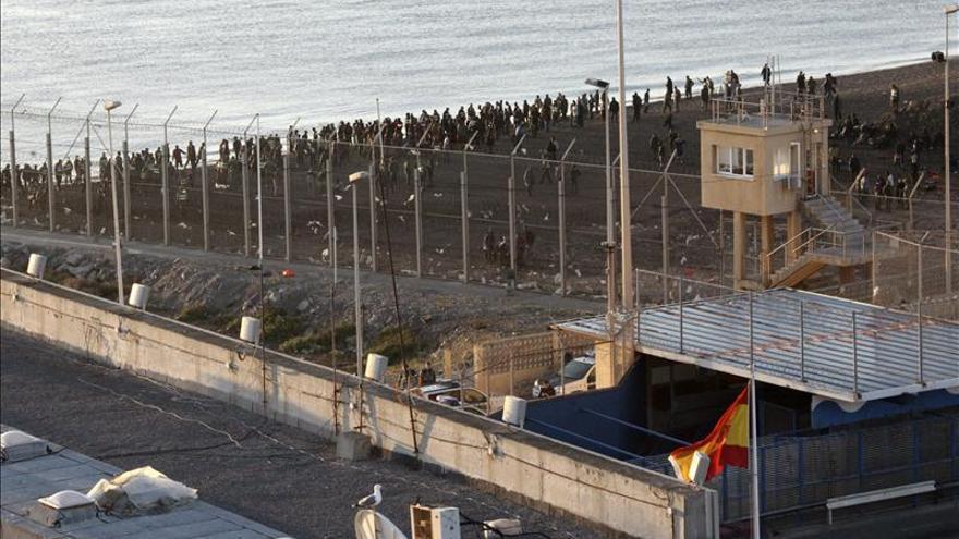 Vista del territorio marroquí desde Ceuta. En el fondo, un grupo de inmigrantes./ Efe