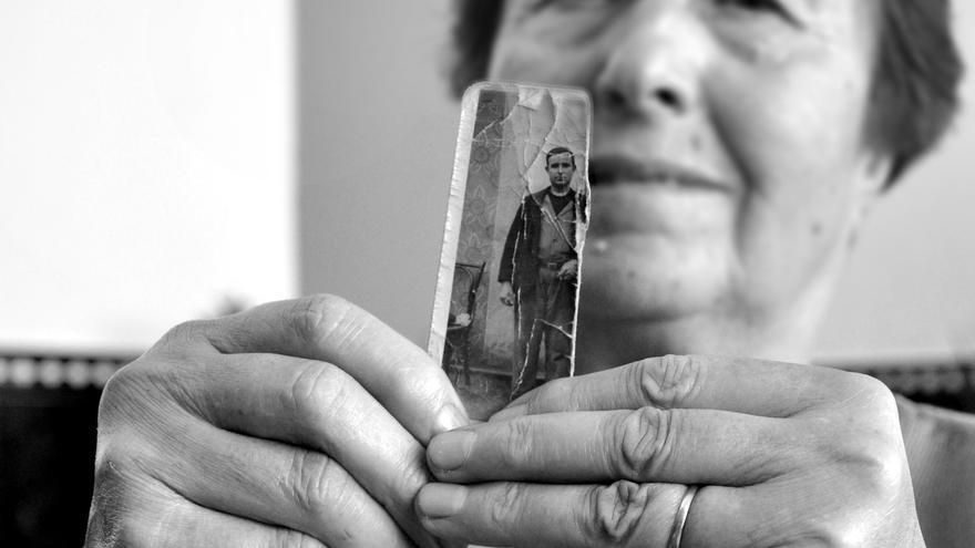 Una víctima del franquismo sostiene una imagen de un familiar asesinado en la Guerra Civil.