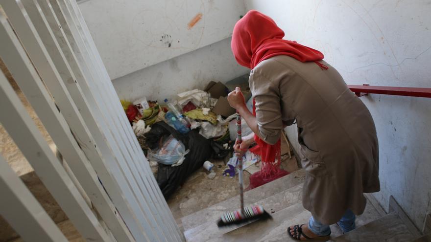 Una mujer barre el hotel abandonado donde duerme junto a 300 personas/ A. S.