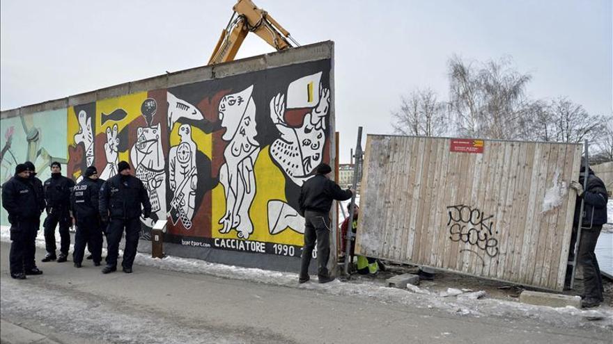 Policías vigilan mientras una máquina excavadora trabaja en la polémica obra de construcción de un edificio de apartamentos justo al lado de una sección del antiguo Muro de Berlín, en Alemania, hoy, miércoles 27 de marzo de 2013.