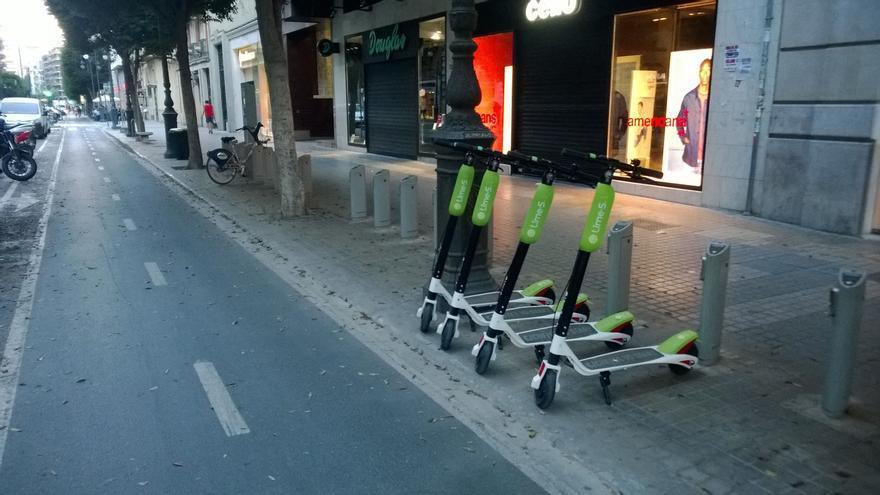 Los nuevos patinetes eléctricos de alquiler en una estación de Valenbisi de la calle Colón