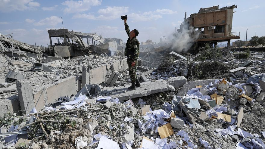 Un soldado sirio graba las ruinas de uno de los centros destruidos por el ataque de EEUU en Damasco. AP Photo/Hassan Ammar