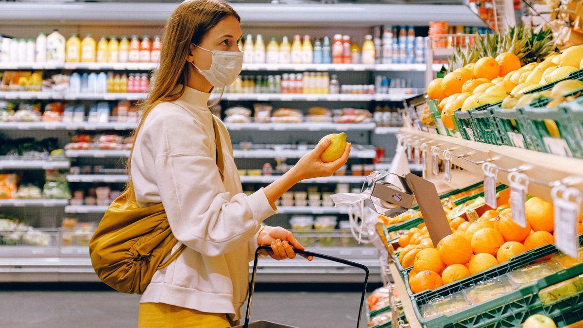 Una mujer elige un limón en un supermercado