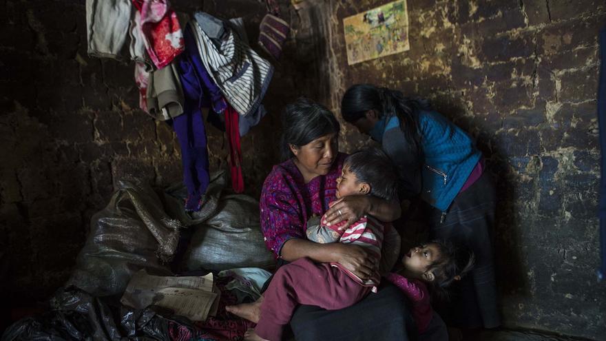 Miembros de la comitiva del gobierno intercambian papeles mientras la madre calma a su hijo con desnutrición