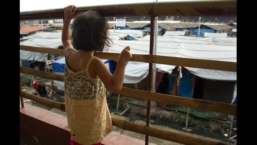 Una niña desplazada contempla el campo de desplazados del polideportivo Joaquín F. Enríquez desde una de las gradas.© Carlos Sardiña Galache.