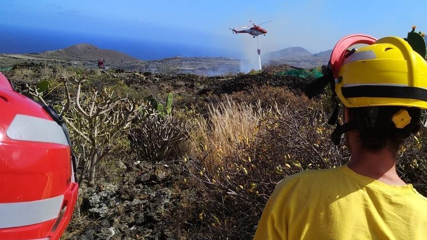 En la imagen, el helicóptero del GES  realiza una descarga de  agua en el fuego registrado este miércoles en una zona de matorrales  del barrio de Los Callejones de Mazo.
