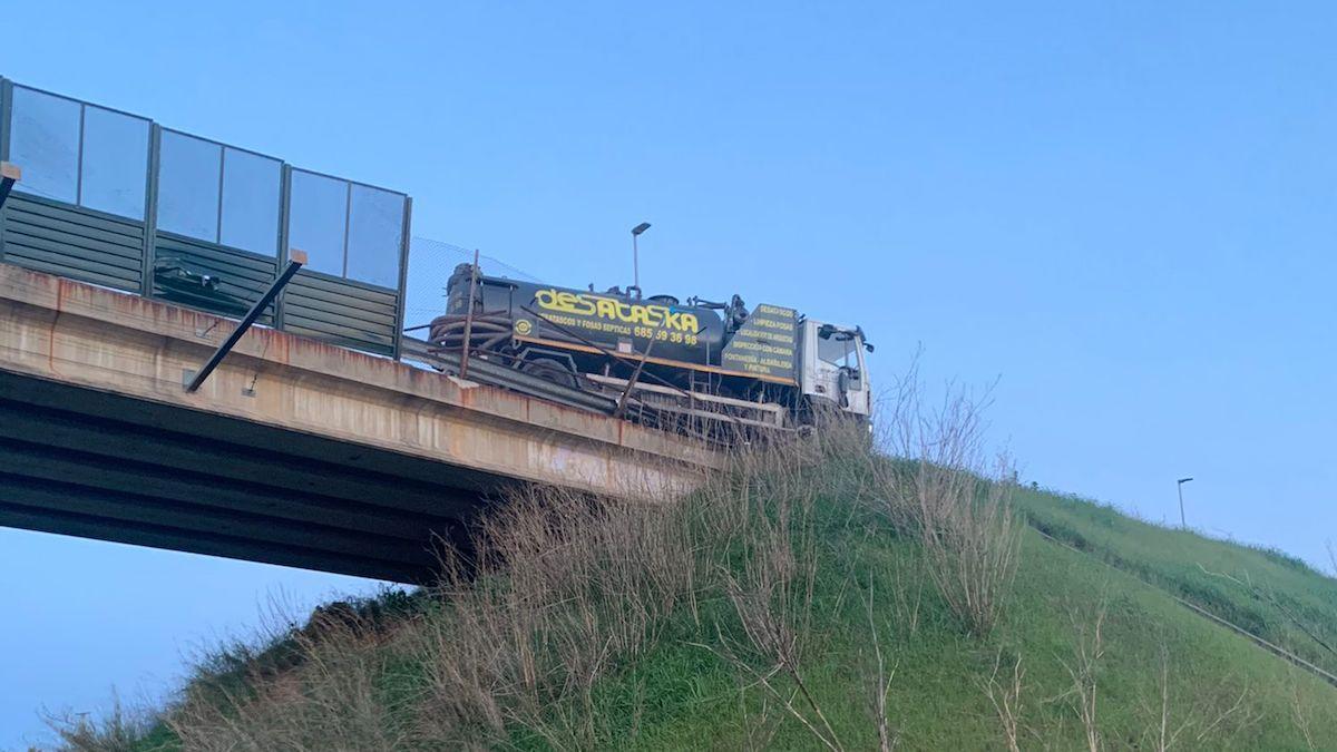 El camión, a punto de despeñarse desde el puente.