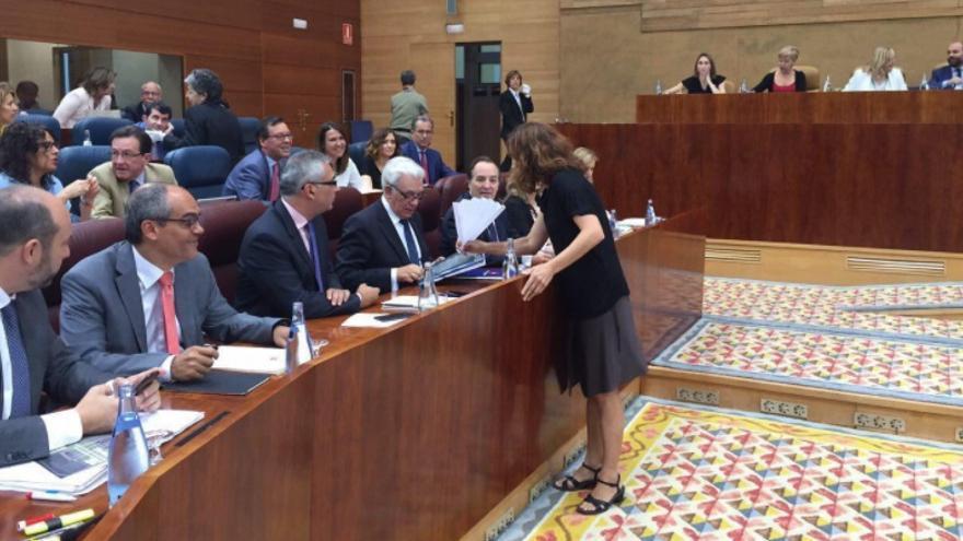 La diputada de Podemos Mónica García entrega al consejero de Sanidad un abanico de papel. / @monicamox1