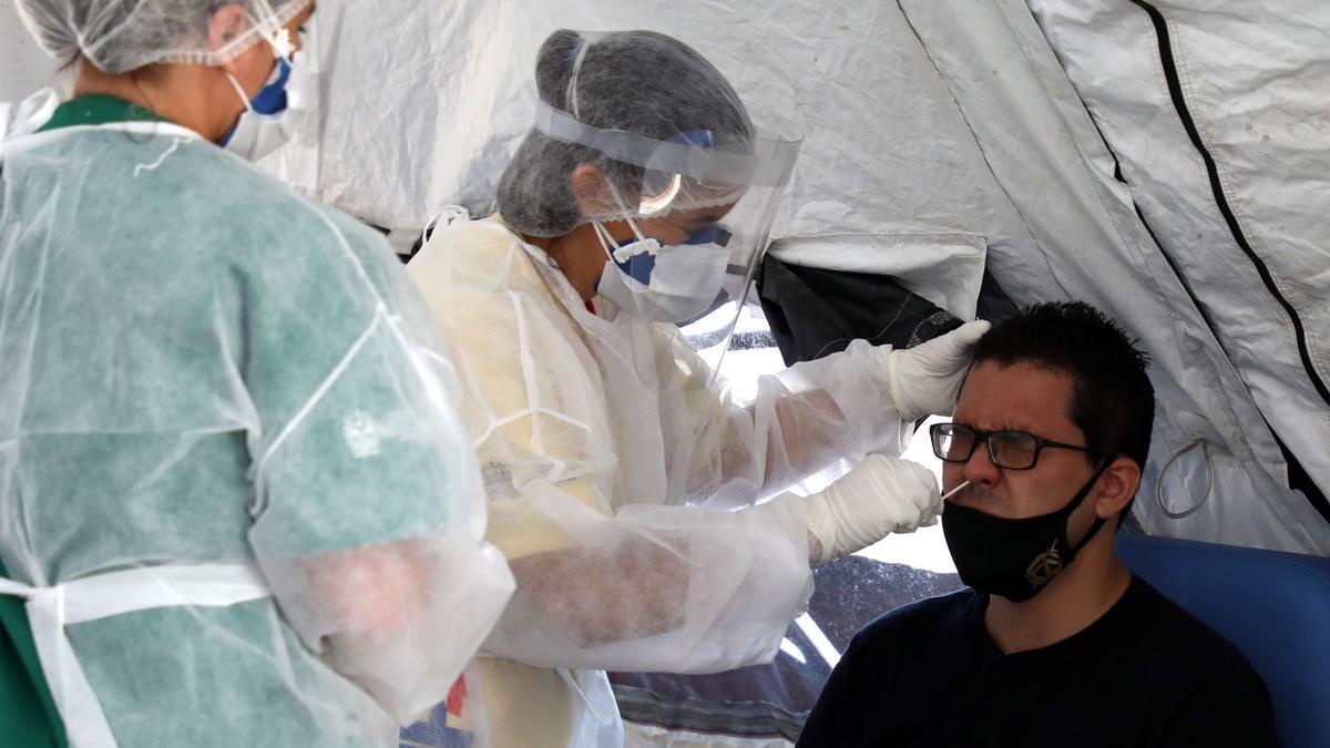 Personal médico realiza la prueba PCR a un hombre