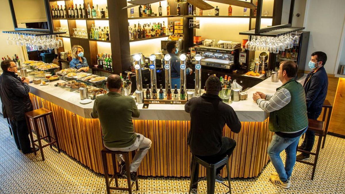 Clientes en la barra de un bar, durante la pandemia.
