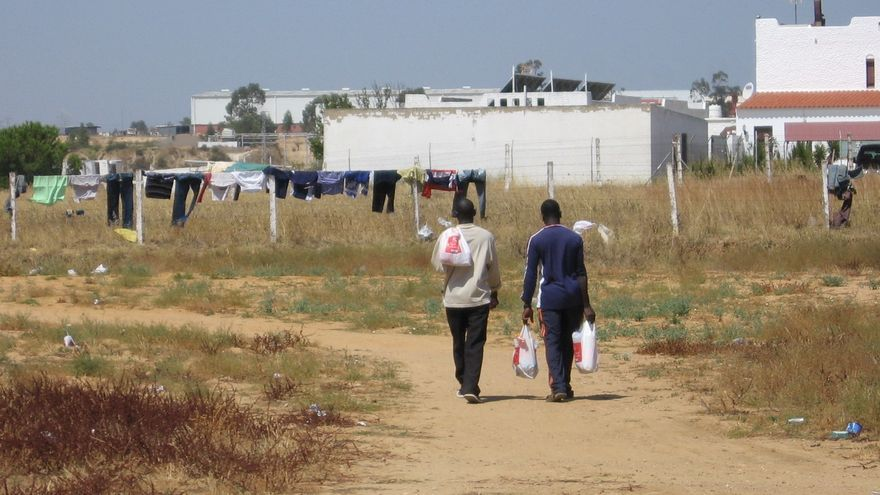 Dos inmigrantes africanos se dirigen al asentamiento que ocupaban en la salida hacia Ayamonte, en Lepe.