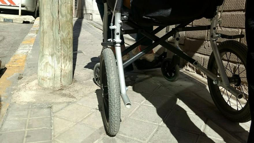La silla de Gloria, intentando pasar por el punto más estrecho de la calle Quesada   SOMOS CHAMBERÍ