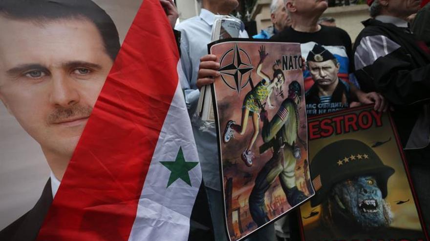 Serbios favorables al presidente sirio, Bashar al Assad, muestran pósters suyos y del presidente ruso, Vladímir Putin, durante una manifestación contra el ataque selectivo por parte de EEUU, Francia y Reino Unido contra posiciones del régimen de Asad.