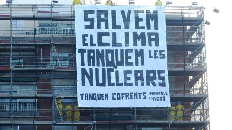 Activistas de la plataforma Tanquem Cofrents cuelgan una pancarta contra las centrales nucleares en la fachada de un edificio en Valencia.