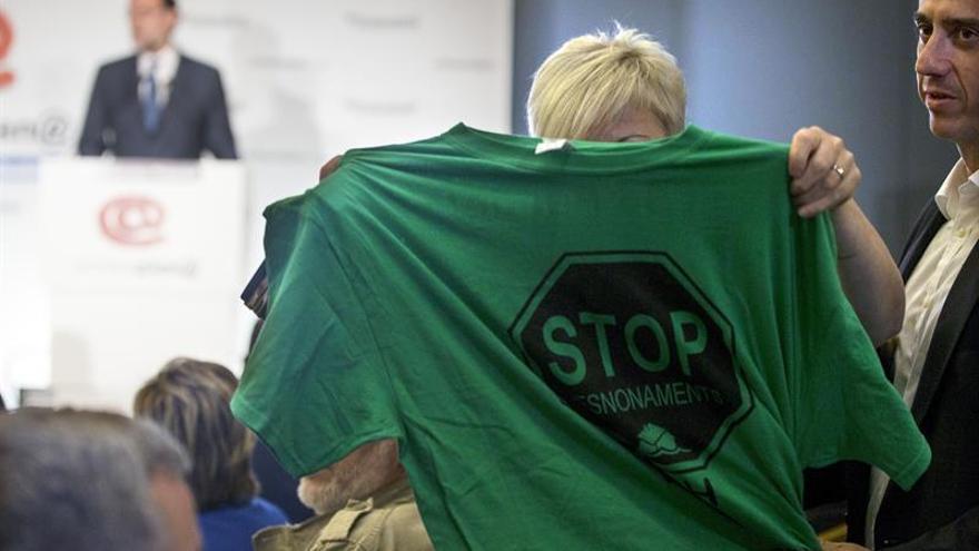 Una activista de la PAH muestra una camiseta alusiva a los desahucios durante la intervención de Rajoy.