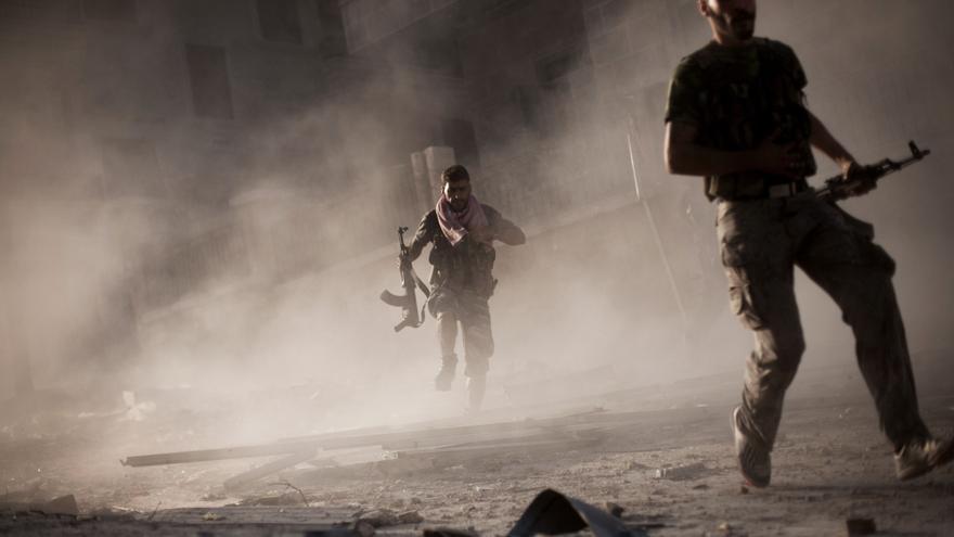 Miembros del Ejército de Liberación de Siria corren después de atacar a un tanque del ejército sirio en el distrito de Izaa, en Aleppo (Viernes, 7 de septiembre de 2012) / AP PHOTO. MANU BRABO