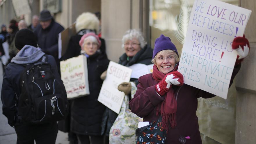 Varias ciudadanas canadienses reciben a un grupo de refugiados. | Efe / Richard Lautens