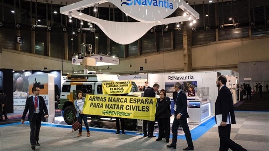Activistas de Greenpeace despliegan una pancarta en el stand de Navantia en la feria de armas HOMSEC.