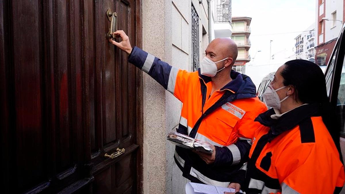 Miembros de Protección Civil en Pozoblanco asisten a personas mayores en casa.