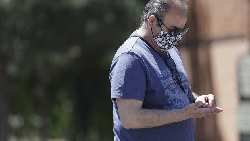 Un hombre camina por la calle protegido con mascarillas.