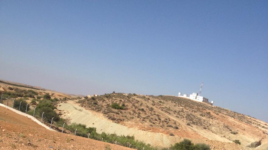 Parte de la valla que Marruecos está construyendo en la frontera con Argelia, a la altura de Oudjda. En lo alto, un puesto de control argelino. / eldiario.es.