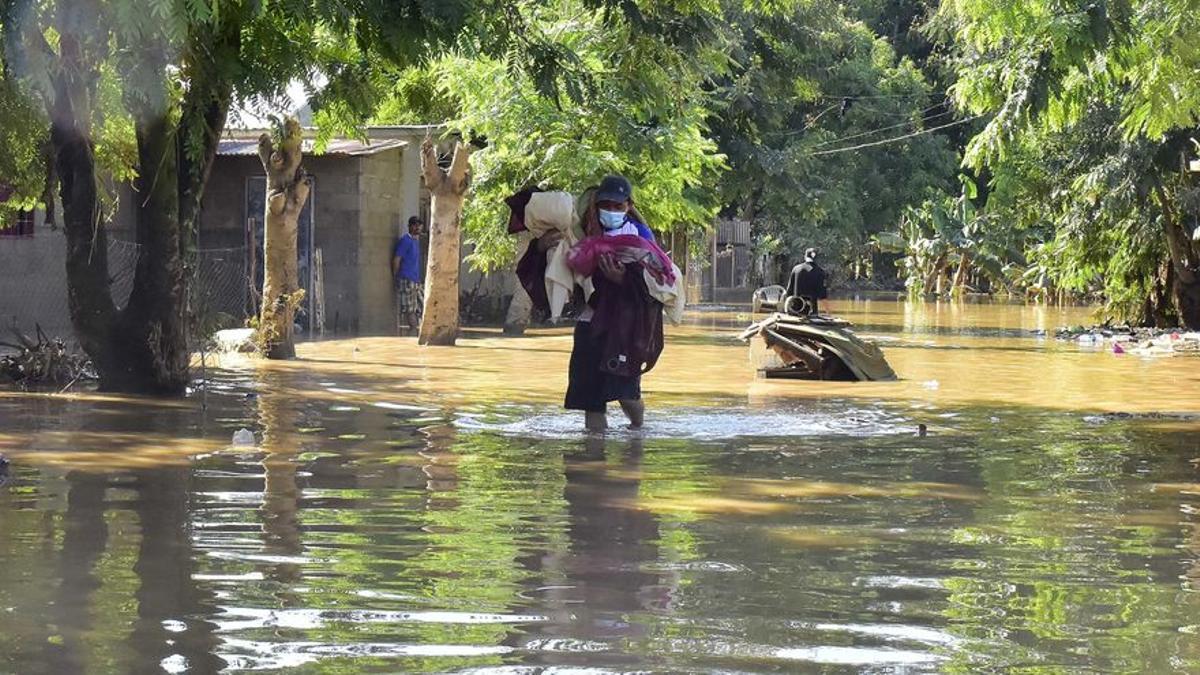 Un hombre camina con sus pertenencias en una de las zonas inundadas durante la temporada de huracanes en Honduras.
