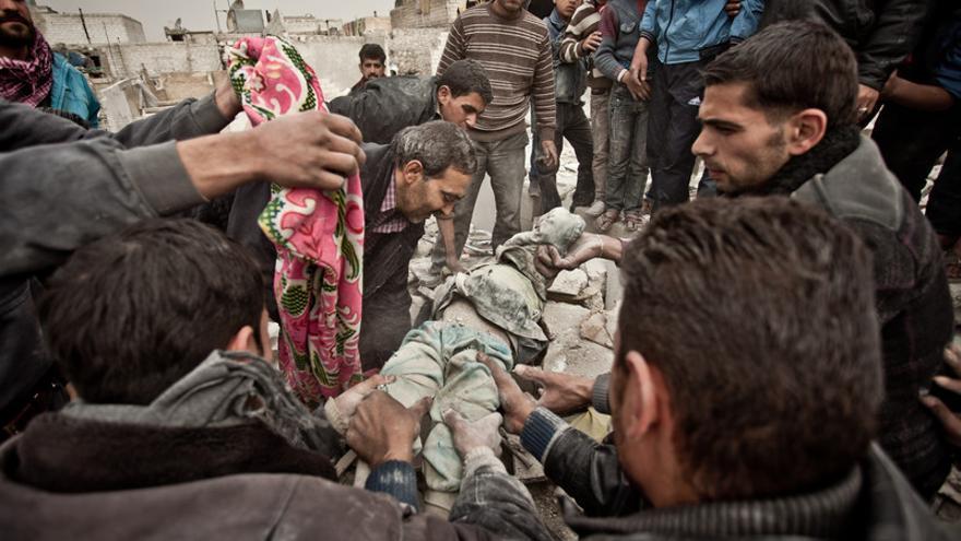 Un grupo de personas recadta el cuerpo de una niña de 6 años entre los escobrosn de una de las viviendas del barrios de Tariq Al AbaUn misil Scud se estrella en el barrio de Tariq Al Bab./Pablo Tosco/Oxfam Intermón