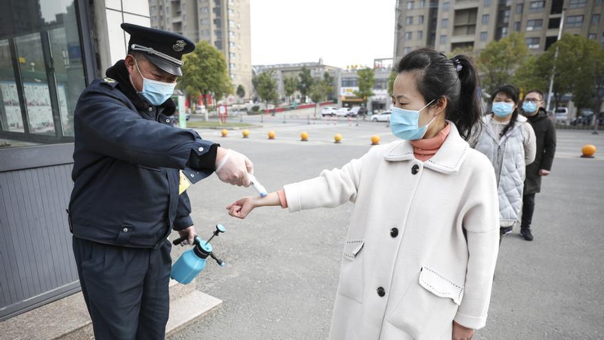 Un trabajador sanitario mide la temperatura a una profesora de una escuela primaria en Jiangsu.