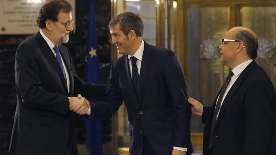 El presidente del Gobierno, Mariano Rajoy (i), durante firma con el secretario general de CC, José Miguel Barragán (d), del acuerdo suscrito entre sus dos partidos sobre los presupuestos generales del Estado de 2017, en un acto al que asiste el jefe del Ejecutivo canario, Fernando Clavijo (c).