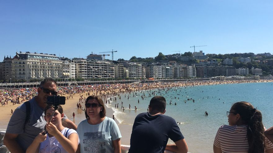 Turistas fotografiándose en la playa de La Concha