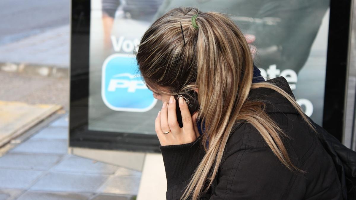 Una mujer habla por teléfono en una parada de autobús.