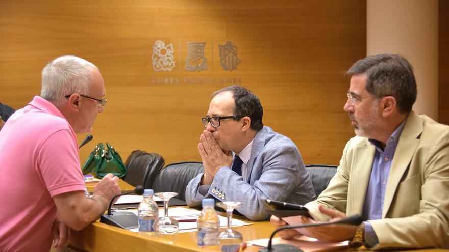 Enrique Soriano, en el centro, conversa con el portavoz de Podemos, Antonio Montiel, en las Corts Valencianes.
