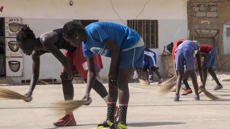 Un grupo de jóvenes barre la cancha de basket en el barrio de Gediawaye (Senegal)