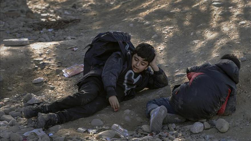 Dos niños migrantes esperaban tumbados en el suelo a obtener permiso para entrar en el campamento de registro y tránsito tras cruzar la frontera entre Grecia y Macedonia, cerca de la ciudad de Gevgelija (Macedonia) el pasado viernes.