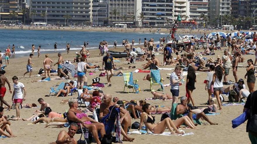 Numerosos turistas y vecinos de Las Palmas de Gran Canaria disfrutan de un día de sol en la playa de Las Canteras