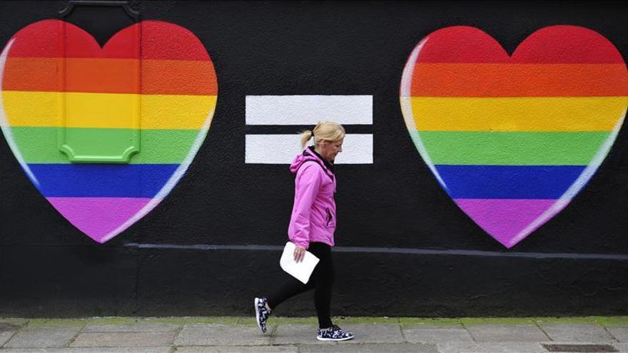 Imagen de archivo de una mujer caminando frente a una pintada de dos corazones con los colores del arcoíris