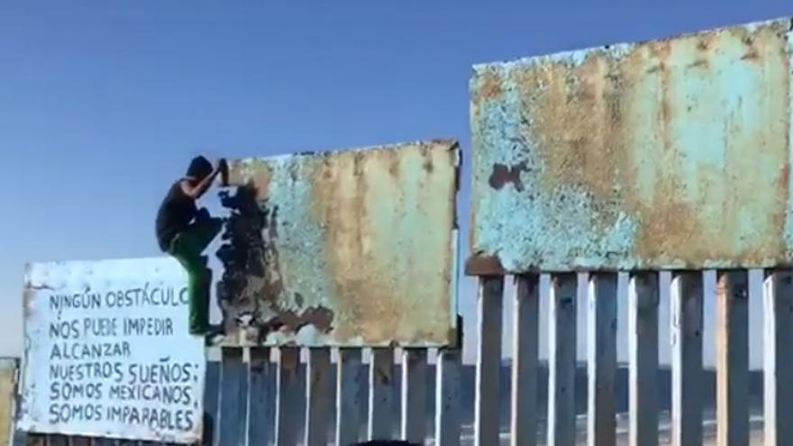 Un hombre trata de escalar la valla con EEUU mientras su compañeros de la caravana le reprueban.