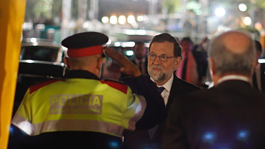 El presidente del Gobierno, Mariano Rajoy, es saludado por un agente de los Mossos