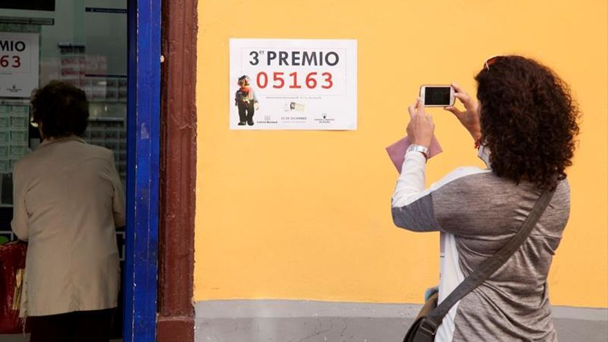 Una mujer fotografía el cartel que acredita que un tercer premio del sorteo de la Lotería de Navidad ha sido vendido en la administración número 9 de Santa Cruz de Tenerife
