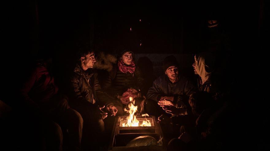 Un grupo de jóvenes afganos, algunos menores de edad, se calientan junto a un fuego en un refugio de montaña la noche antes de cruzar la frontera con Croacia