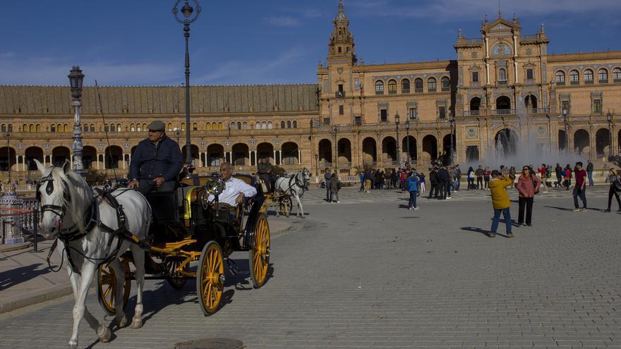 Un coche de caballos abandona la Plaza de España, otro e los emblemas monumentales de Sevilla. Viajar Ahora