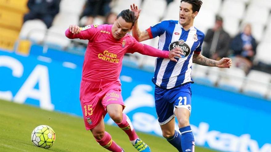 El centrocampista de la UD Las Palmas, Roque Mesa (i), controla la pelota ante el centrocampista del Deportivo de La Coruña, Luis Alberto Romero (d), durante el encuentro correspondiente a la trigésimo segunda jornada de la Liga BBVA, que enfrentó al R.C. Deportivo de La Coruña y a la U.D. Las Palmas en el estadio de Riazor. EFE/Cabalar